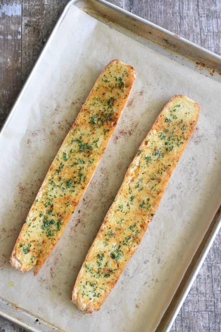 Baked garlic bread on baking sheet