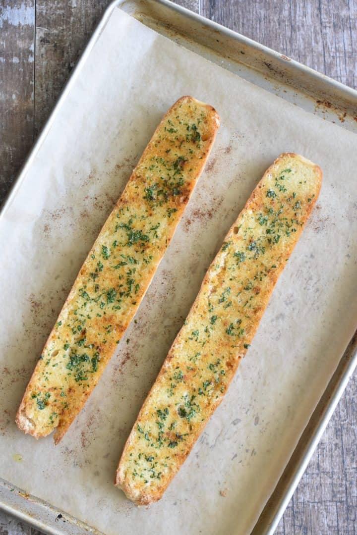 Baked garlic bread on baking sheet