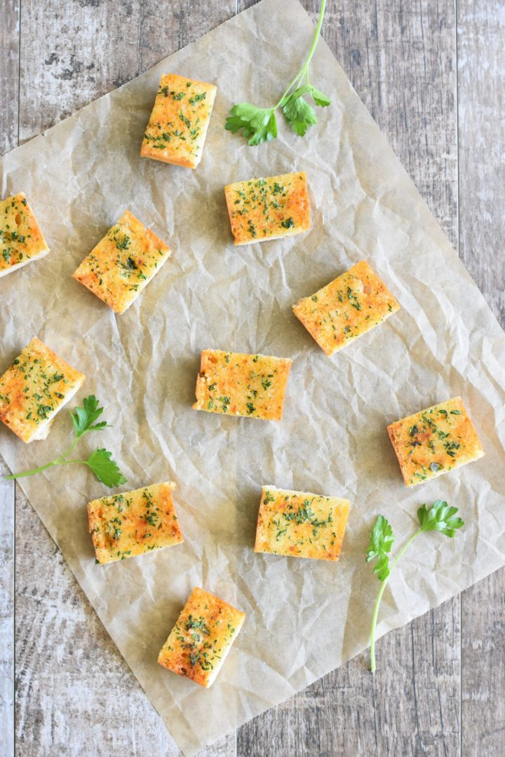Overhead shot of cut pieces of garlic bread on a piece of parchment with parsley sprigs