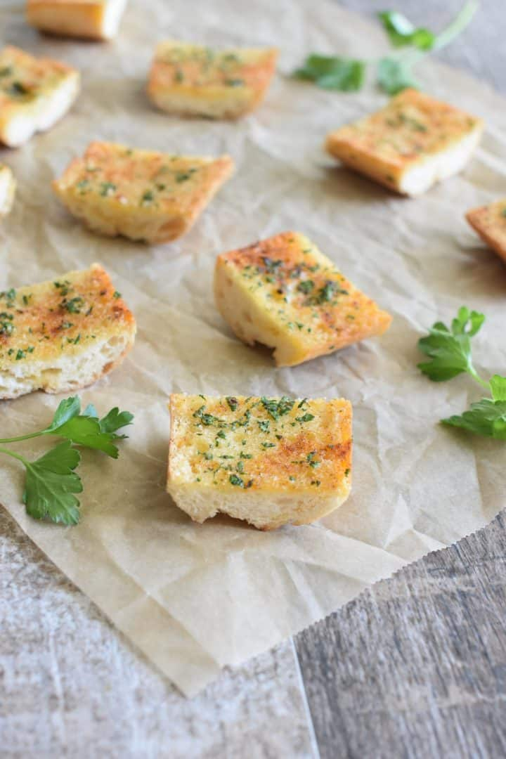 Close up of cut pieces of garlic bread on a piece of parchment with parsley sprigs