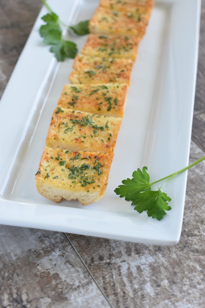 Close up of cut pieces of garlic bread on white serving platter with parsley sprigs