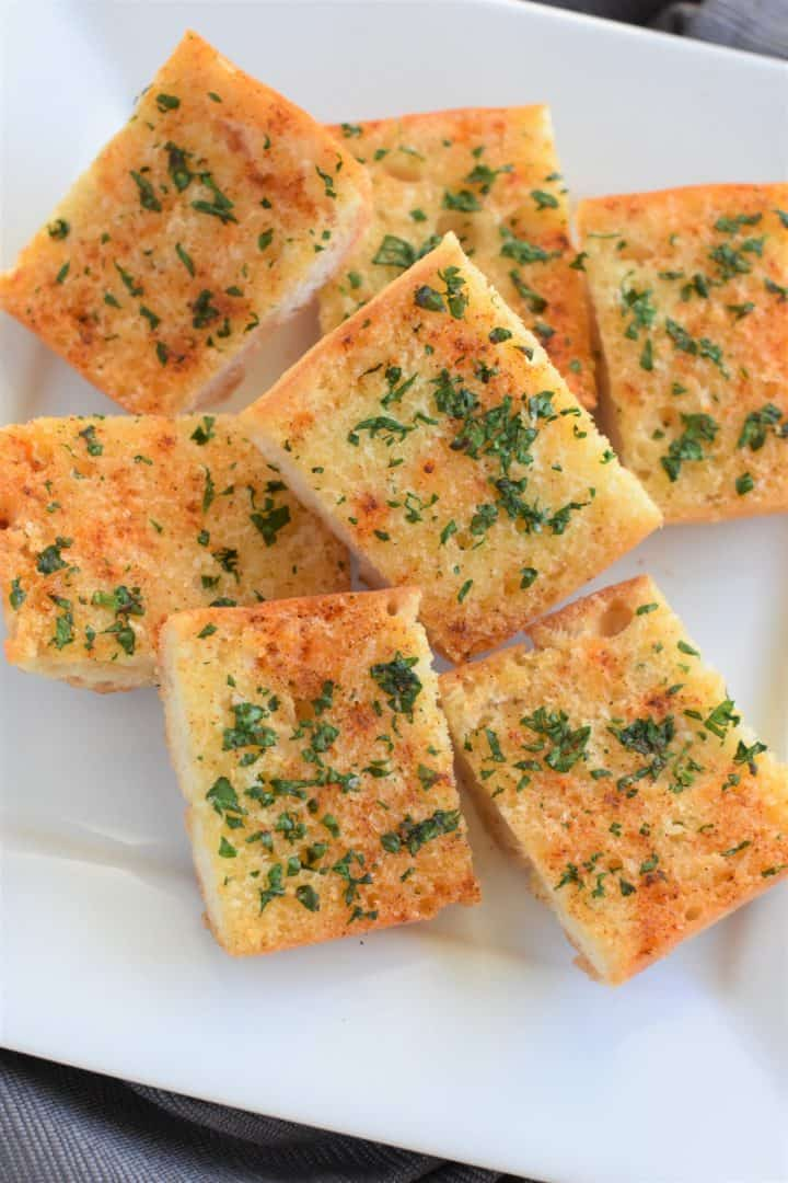 Cut pieces of vegan and gluten-free garlic bread on a white plate