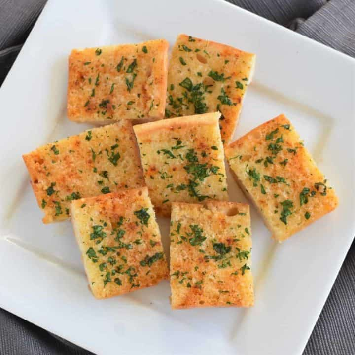 overhead view of cut pieces of garlic bread on a white plate