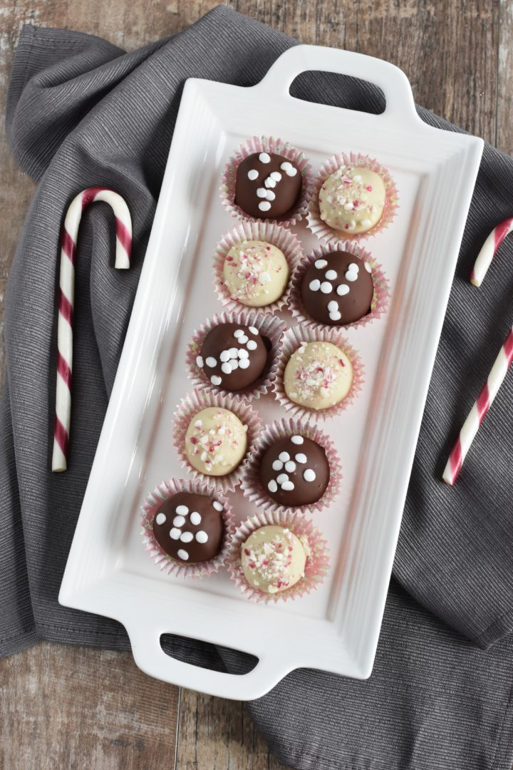 overhead of truffles on white serving platter on kitchen towel with candy canes next to it