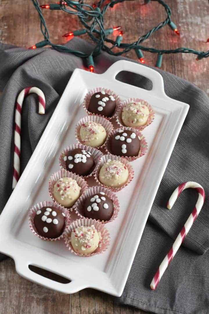 Truffles on white serving platter on kitchen napkin with candy canes next to it and with red Christmas lights in background