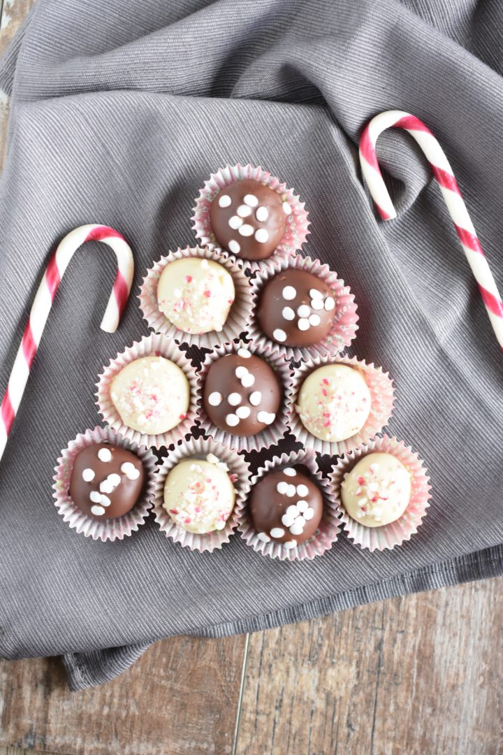 Truffles on a kitchen towel in the shape of a Christmas tree with candy canes around the display