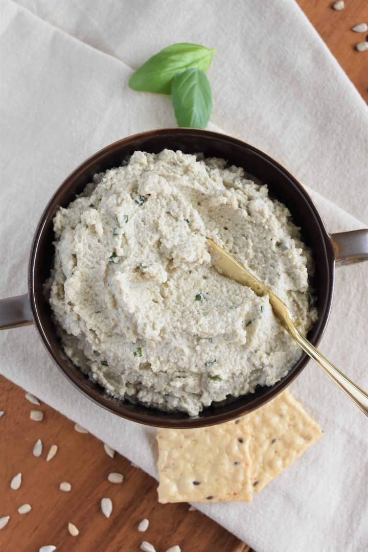 overhead of sunflower seed ricotta with spreading knife in the bowl and crackers, basil and sunflower seeds surrounding it
