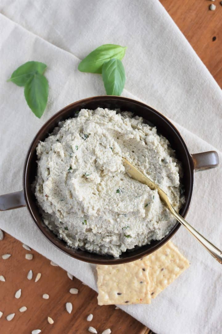 overhead of vegan ricotta with spreading knife in the bowl and basil, crackers and sunflower seeds surrounding it