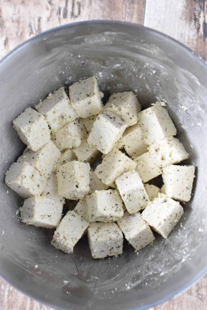 Tofu combined with cornstarch mixture in mixing bowl