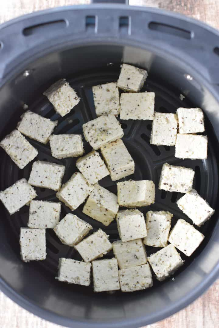 Tofu added to air fryer basket with crisper plate inserted