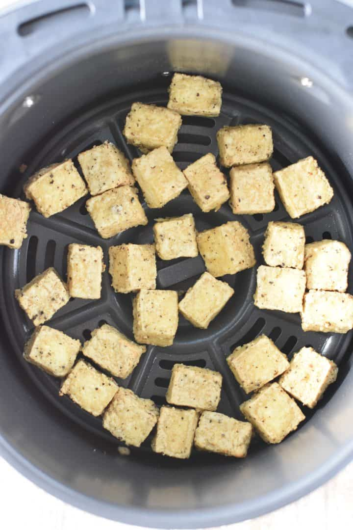 Cooked tofu in air fryer basket after air frying