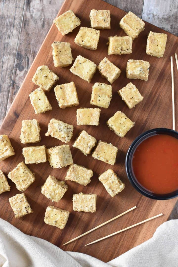 overhead of tofu on a serving board with dipping sauce next to the pieces and serving toothpicks in the background