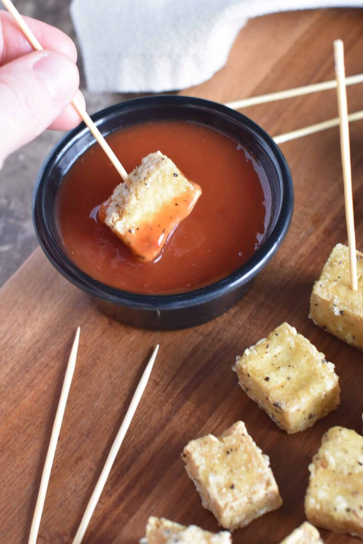 Dipping a piece of tofu into sweet chili sauce with a serving toothpick