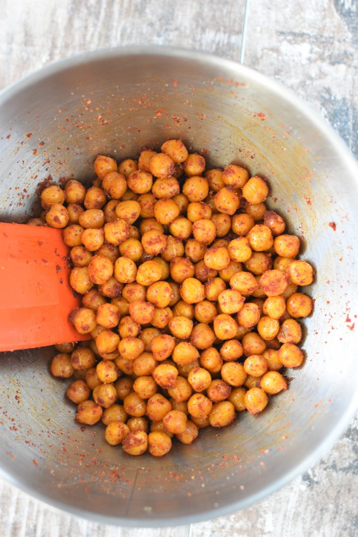 Chickpeas combined with BBQ seasoning in mixing bowl