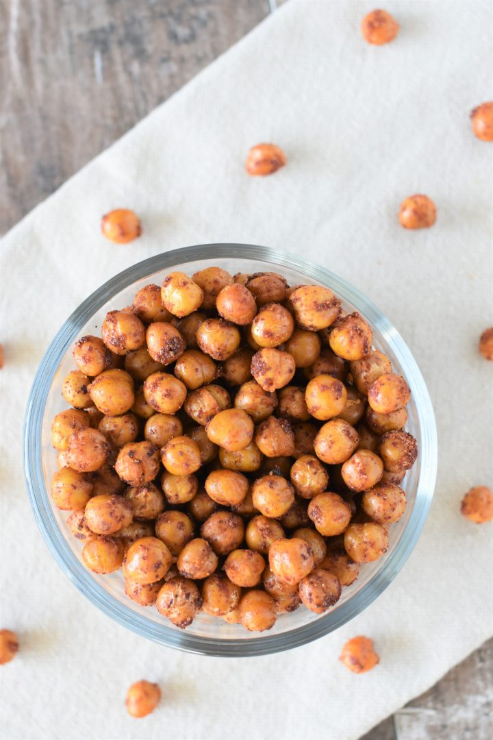 overhead of BBQ chickpeas in bowl on kitchen towel with some on the towel