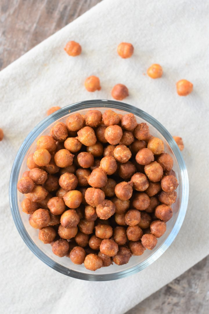 Overhead of Buffalo chickpeas in small bowl on kitchen towel with some on the towel