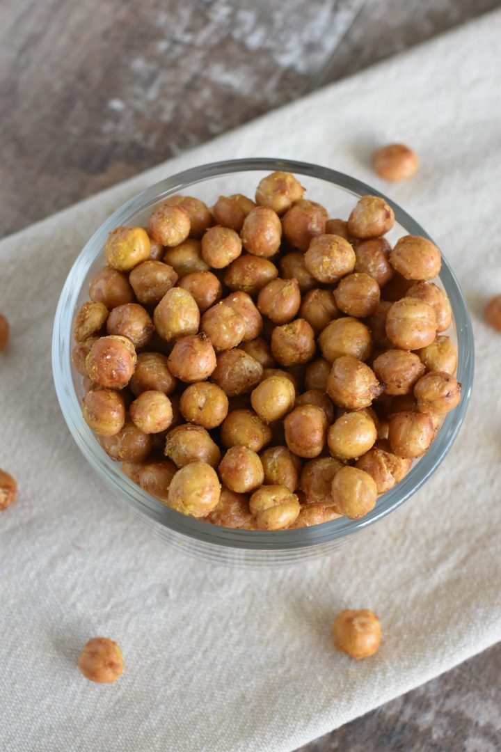 Chickpeas in bowl on kitchen towel with some on the towel