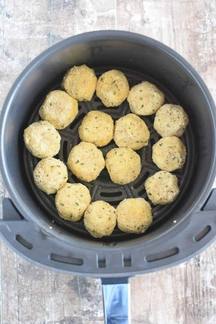 Potato balls added to air fryer basket and sprayed lightly with olive oil spray