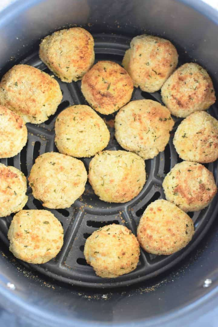 Cooked potato balls in air fryer basket