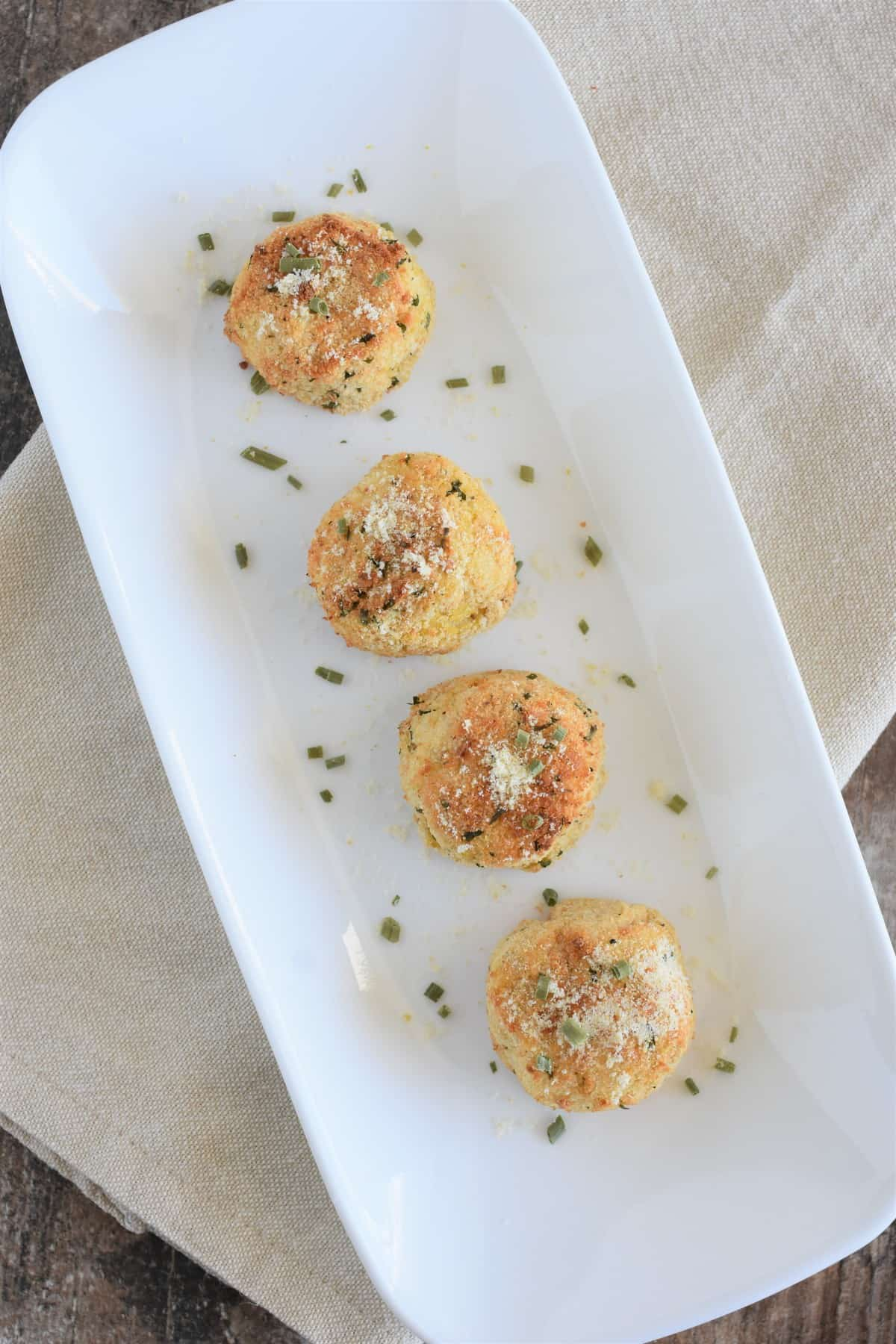 Overhead shot of potato balls on white serving dish garnished with vegan Parmesan and chives