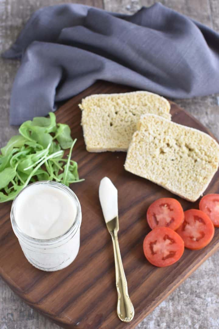 view of mayo in mason jar with spreading knife, arugula, tomatoes and bread all on a wooden board
