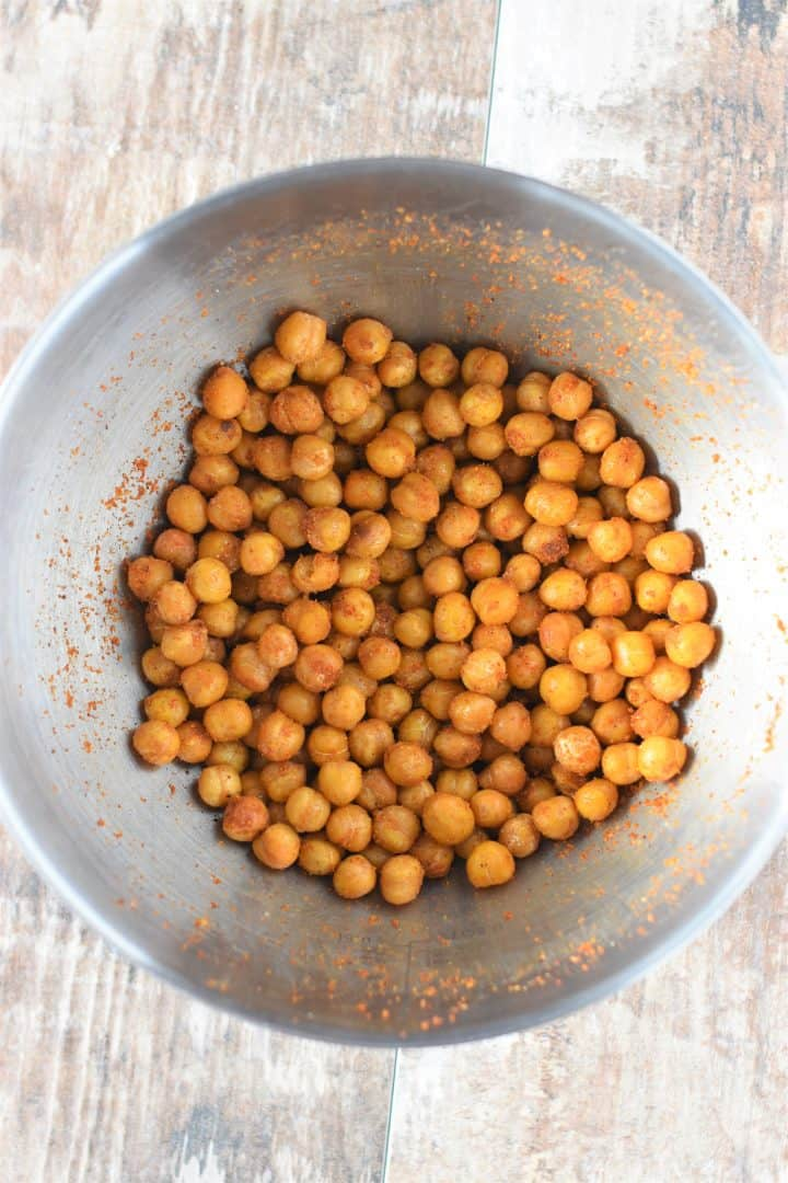Chickpeas mixed with taco fiesta seasoning in mixing bowl