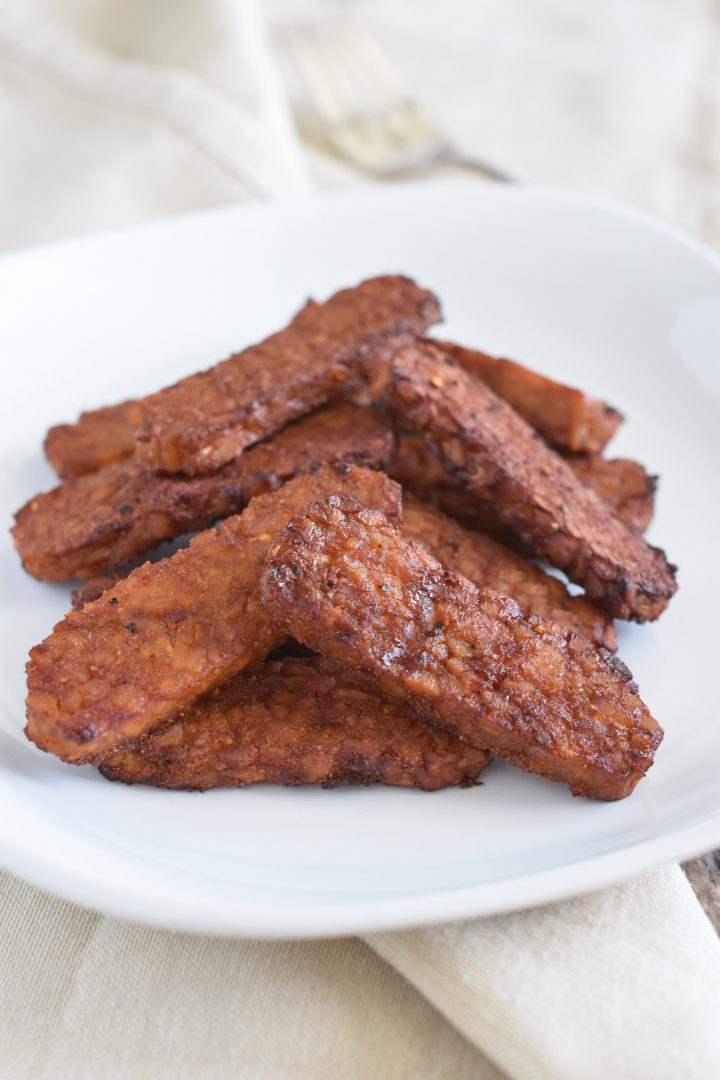 Tempeh bacon on white plate on top of kitchen napkins