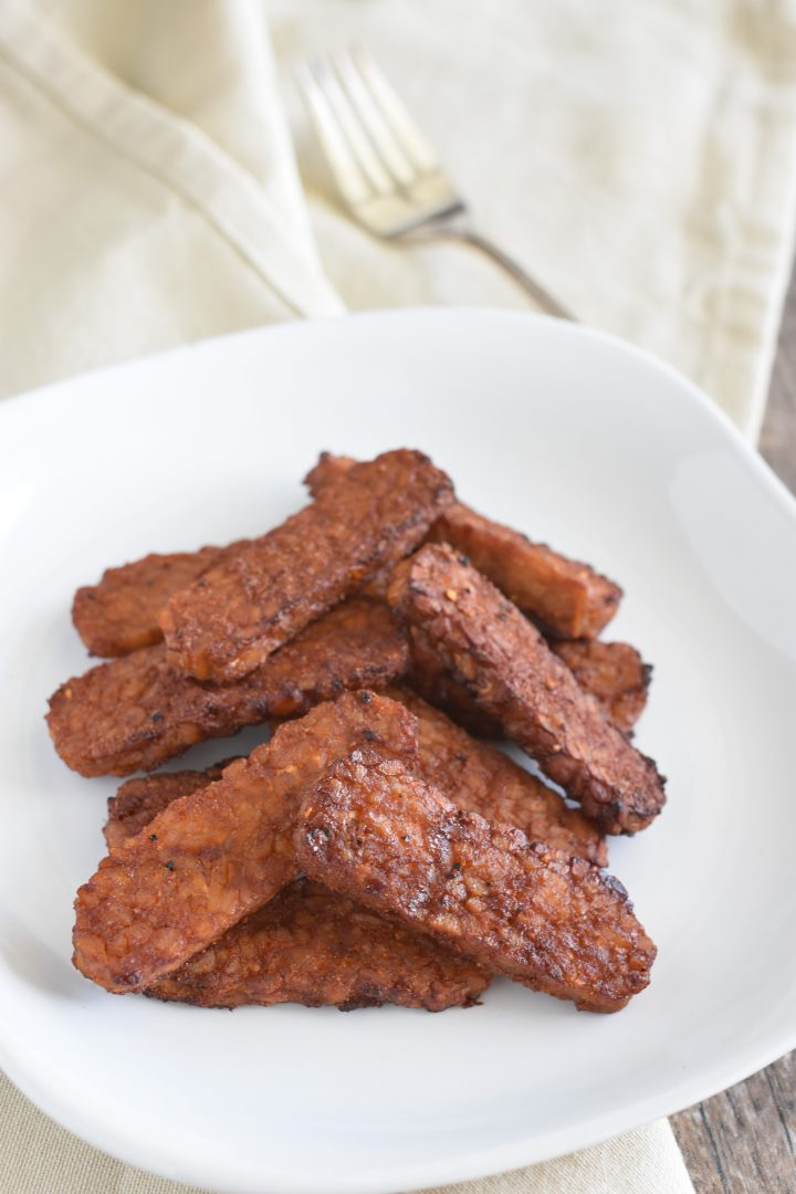 cooked tempeh on a white plate on a kitchen napkin with fork in the background