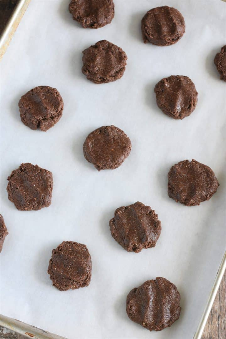 Pressed down and reshaped cookies on parchment-lined baking sheet
