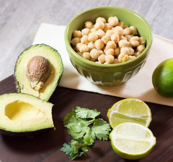 Avocado, chickpeas, cilantro and lime on a wooden board