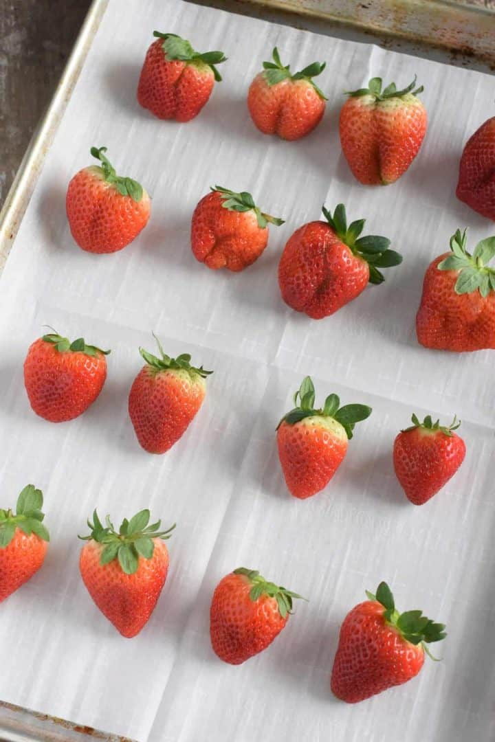 strawberries on a parchment-lined baking sheet ready to be dipped