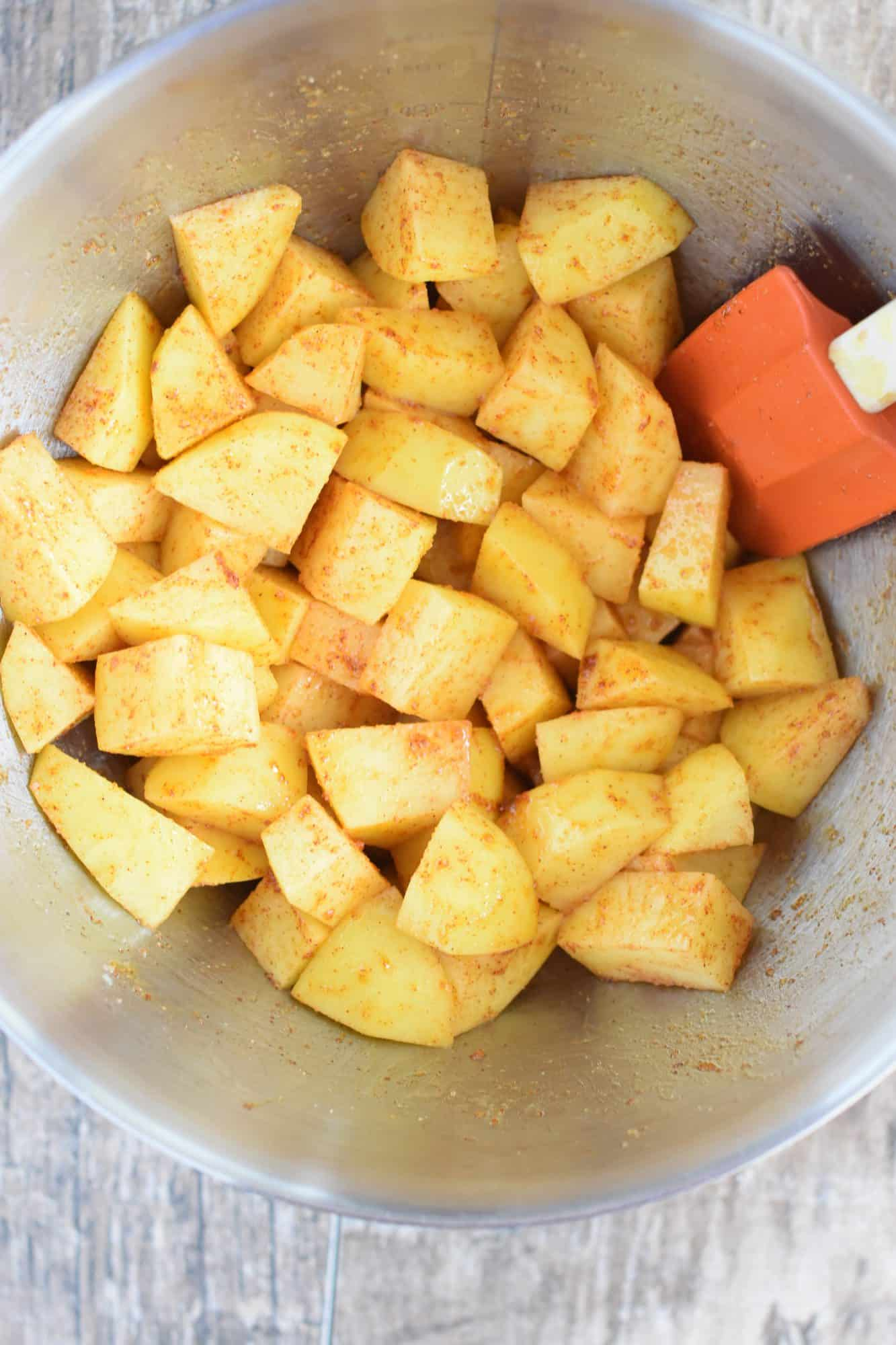 olive oil, paprika, onion powder and salt mixed into the potatoes