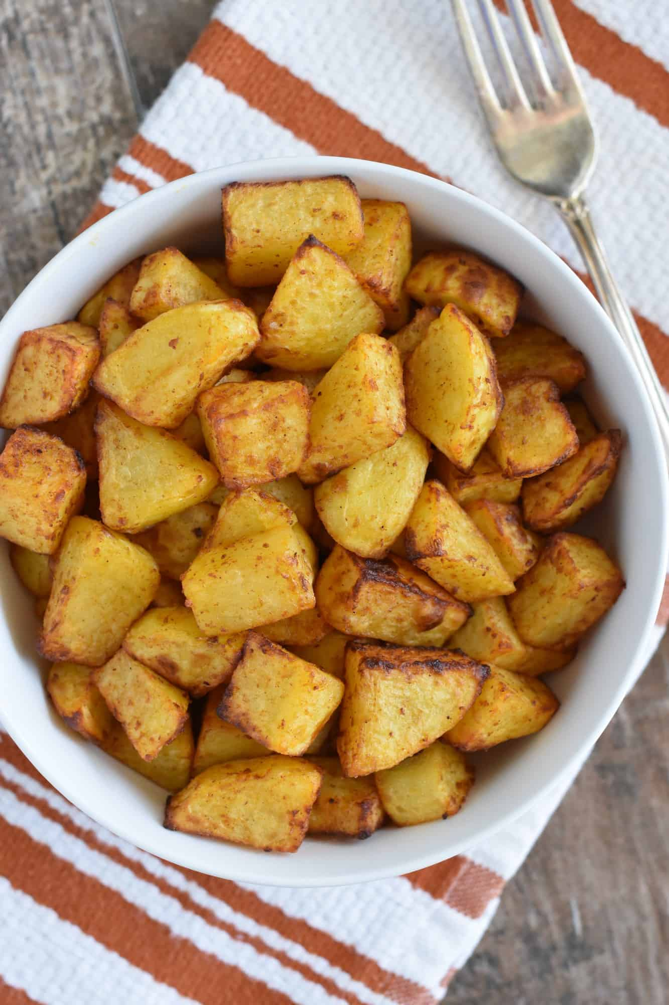 air fryer home fries in white serving bowl with fork next to it