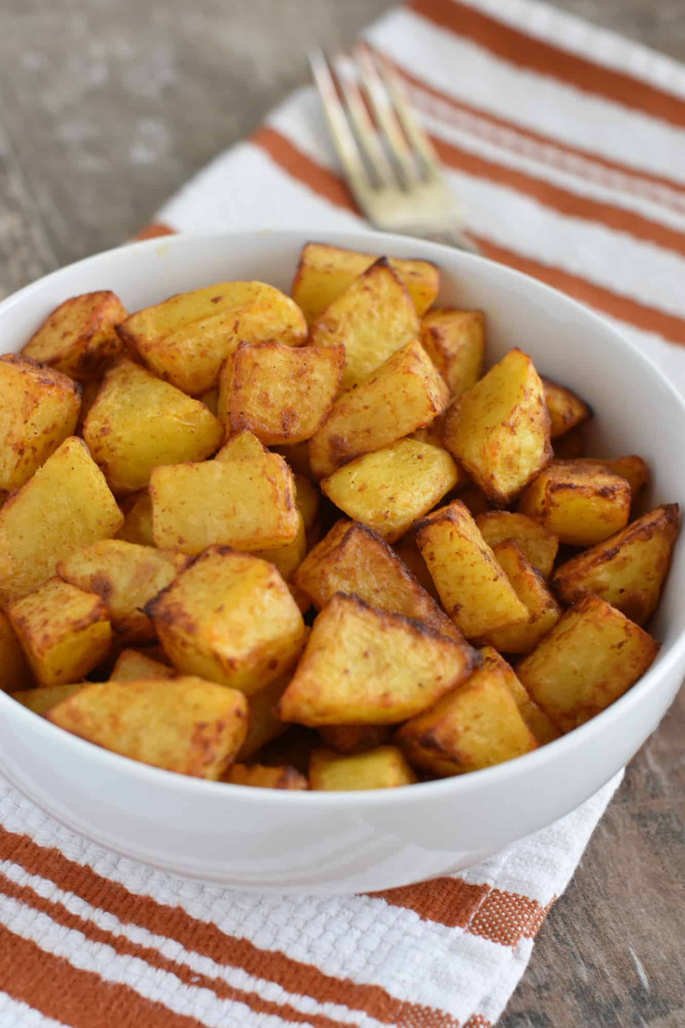 breakfast potatoes in white serving bowl with fork behind it