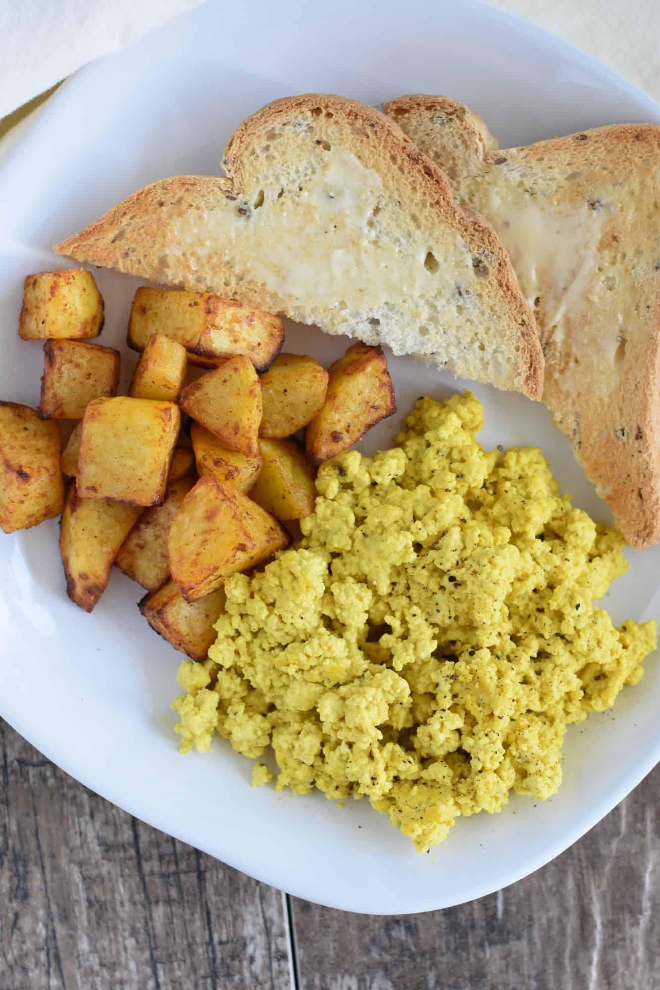 potatoes on a white plate next to tofu scramble and toast