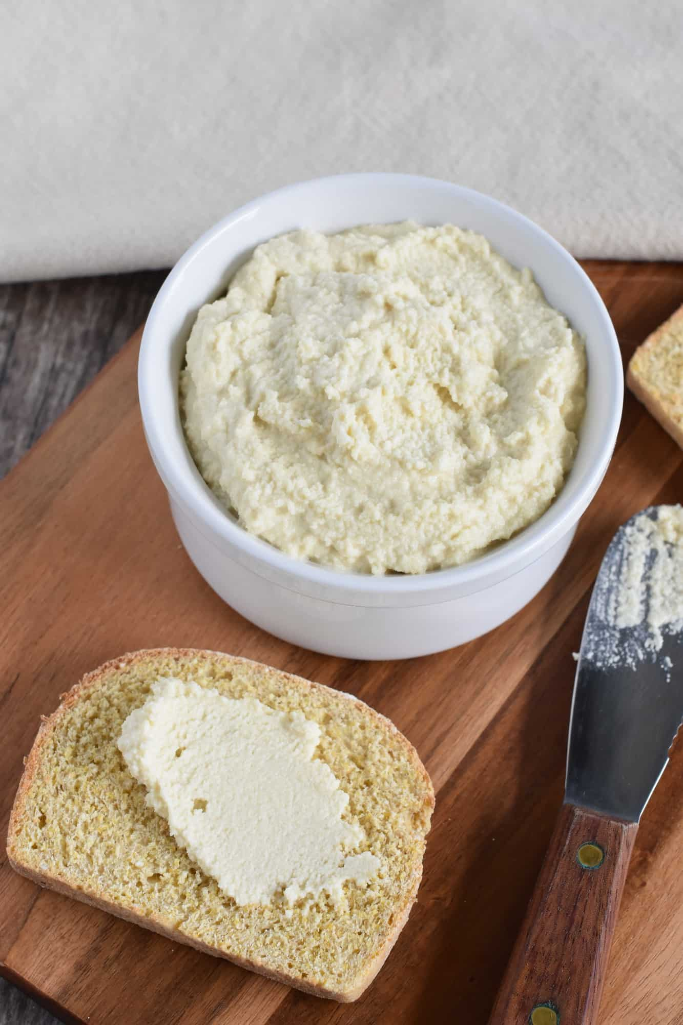 some almond cheese spread on a piece of gluten-free bread with the knife next to it and the rest of the cheese in a bowl behind it
