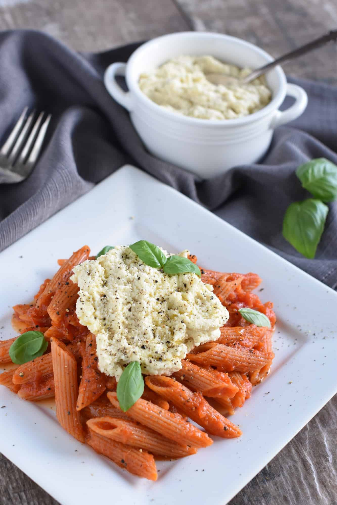 easy vegan pasta with ricotta on a white plate with a fork next to it and ricotta in the background