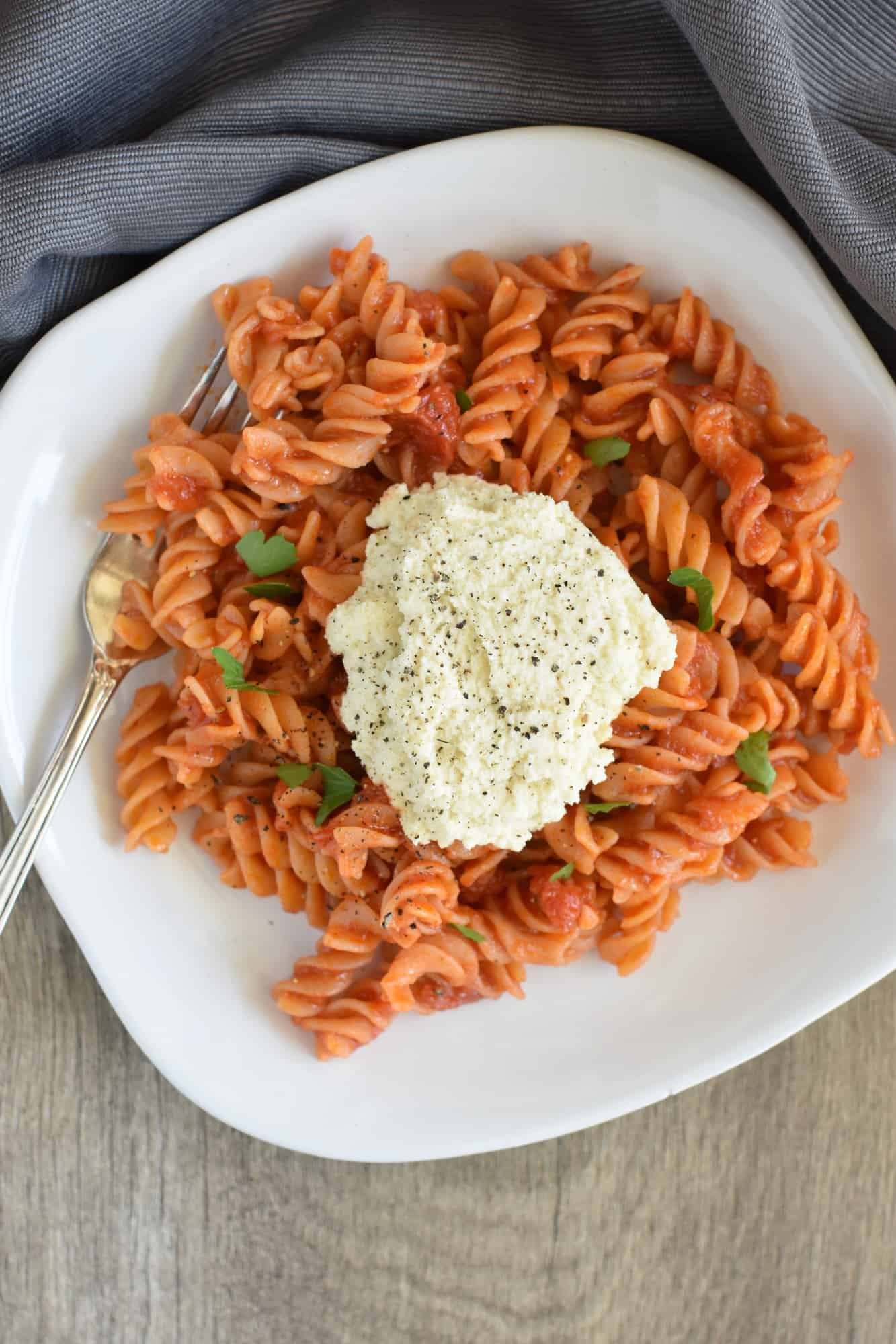 overhead view of rotini with dollop of ricotta and fork on the plate