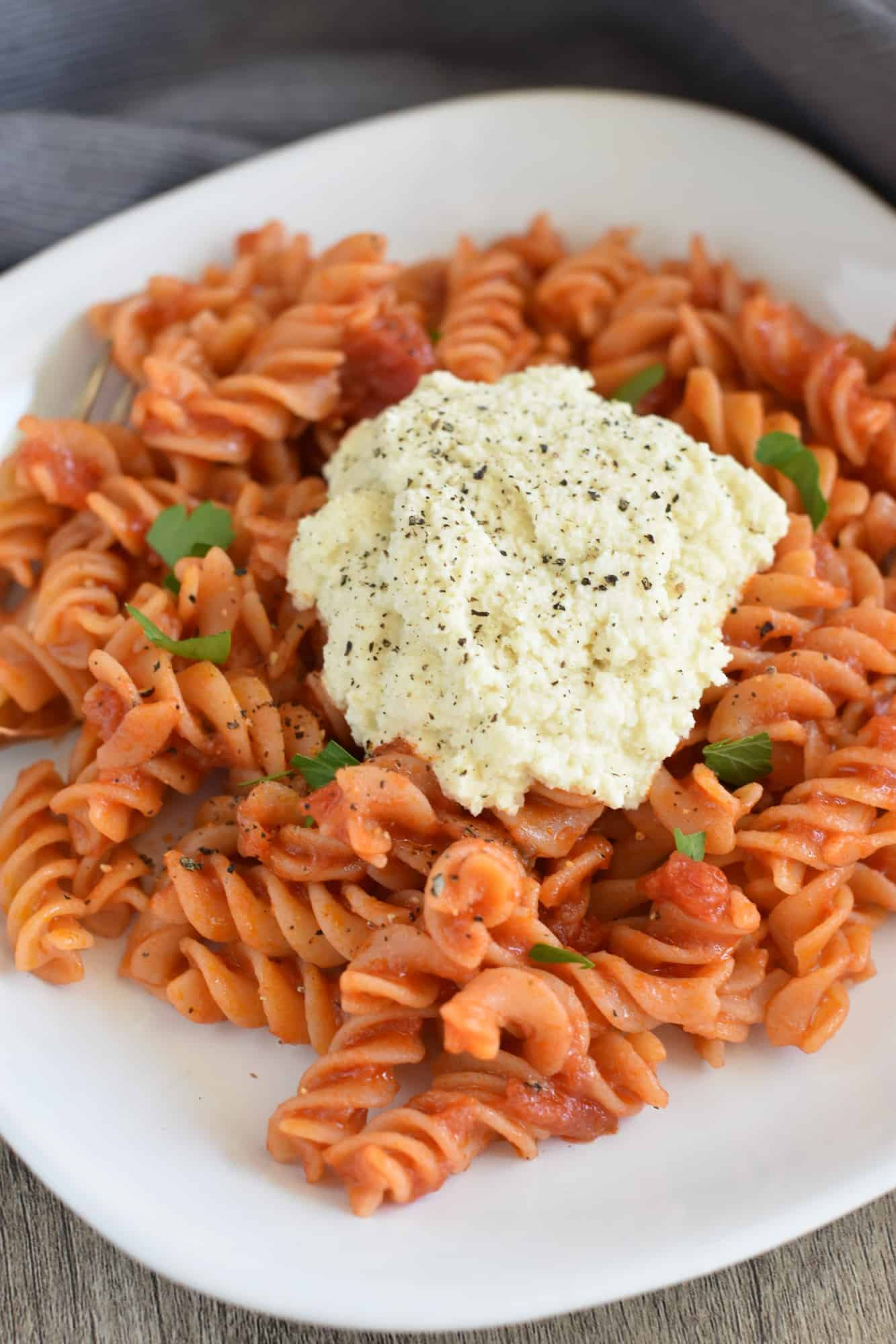 rotini pasta with almond ricotta on a white plate