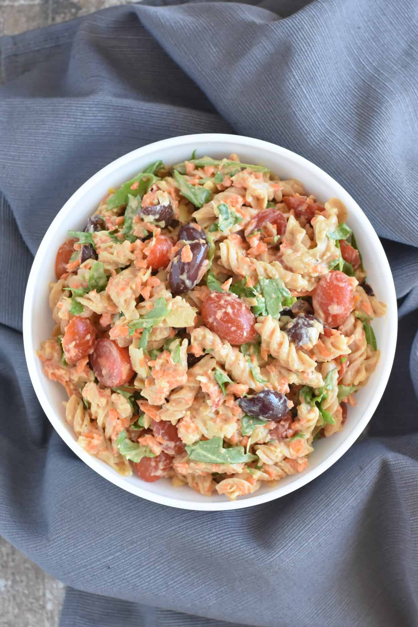 overhead of pasta salad in a bowl on a grey napkin