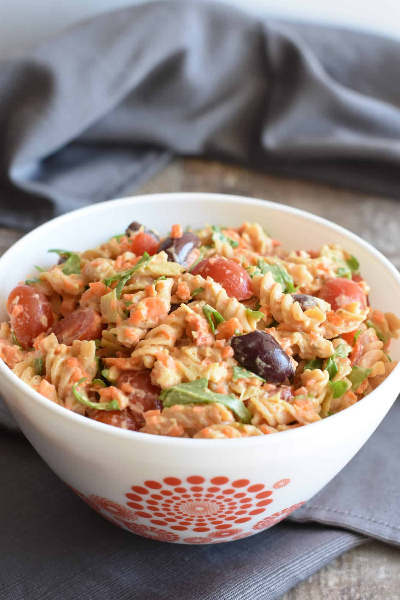 front view of pasta salad in a white bowl with red designs