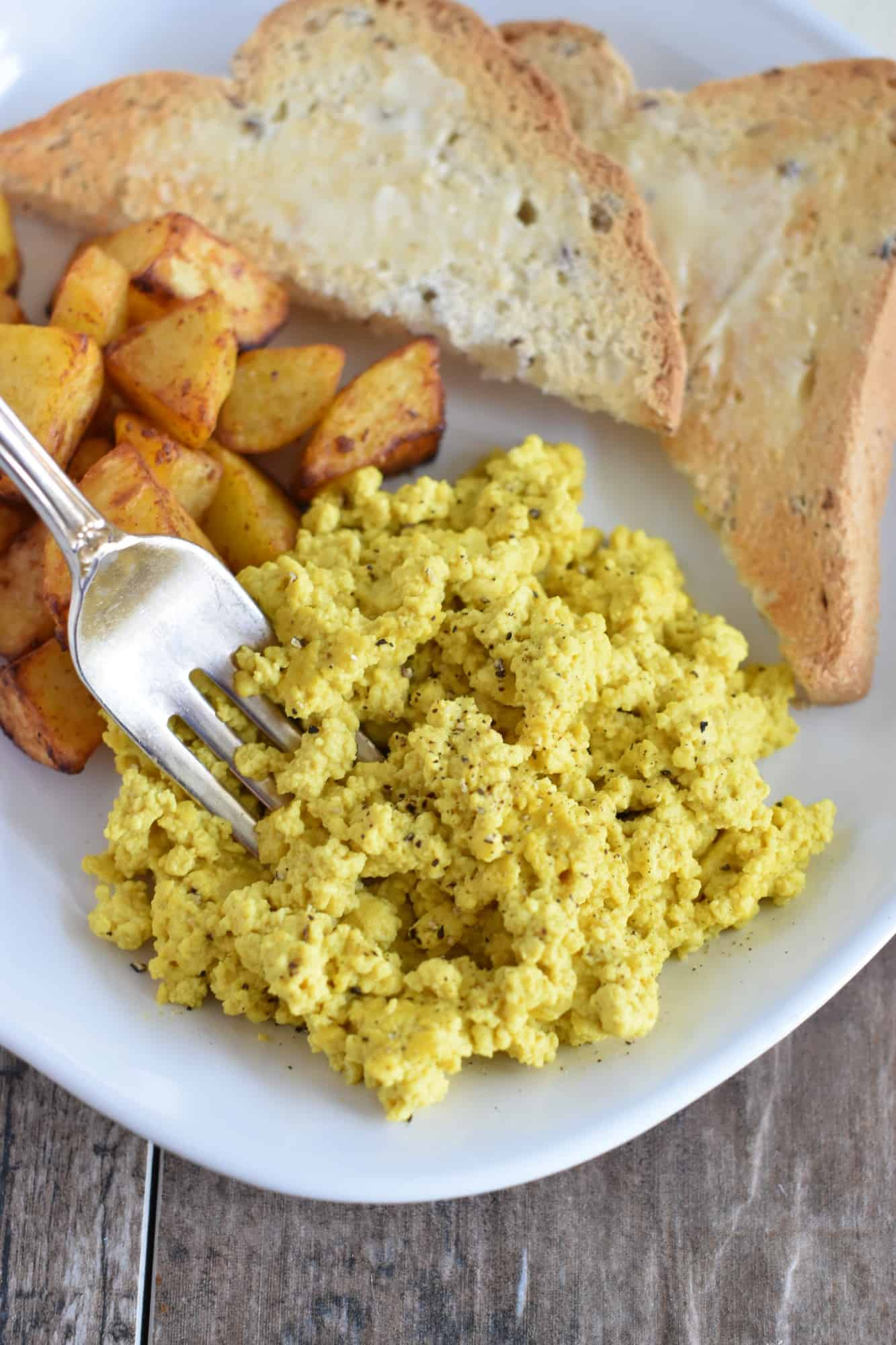 taking some vegan tofu scramble with a fork with potatoes and toast behind it on the same plate