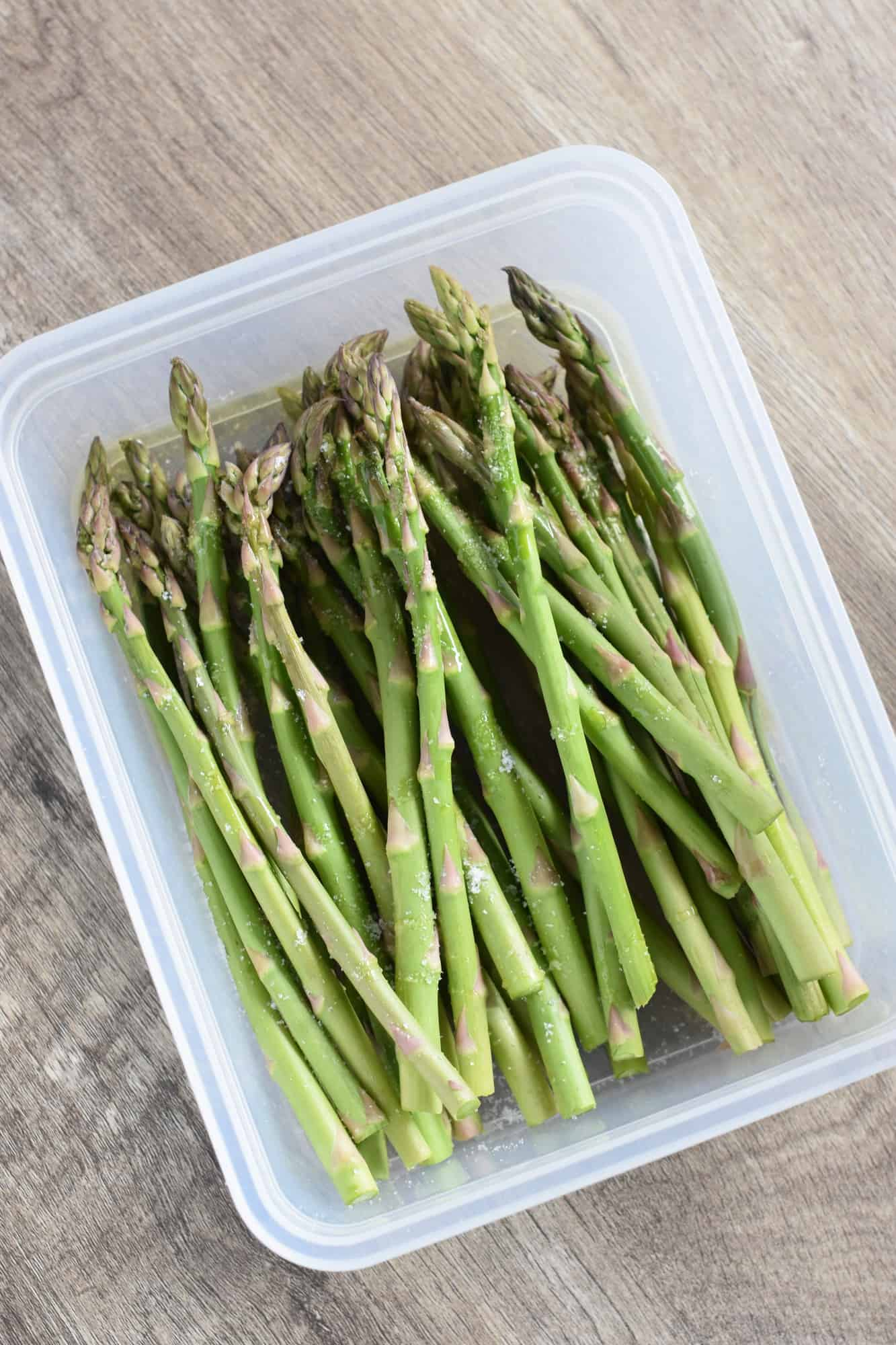 Asparagus in container with olive oil in salt