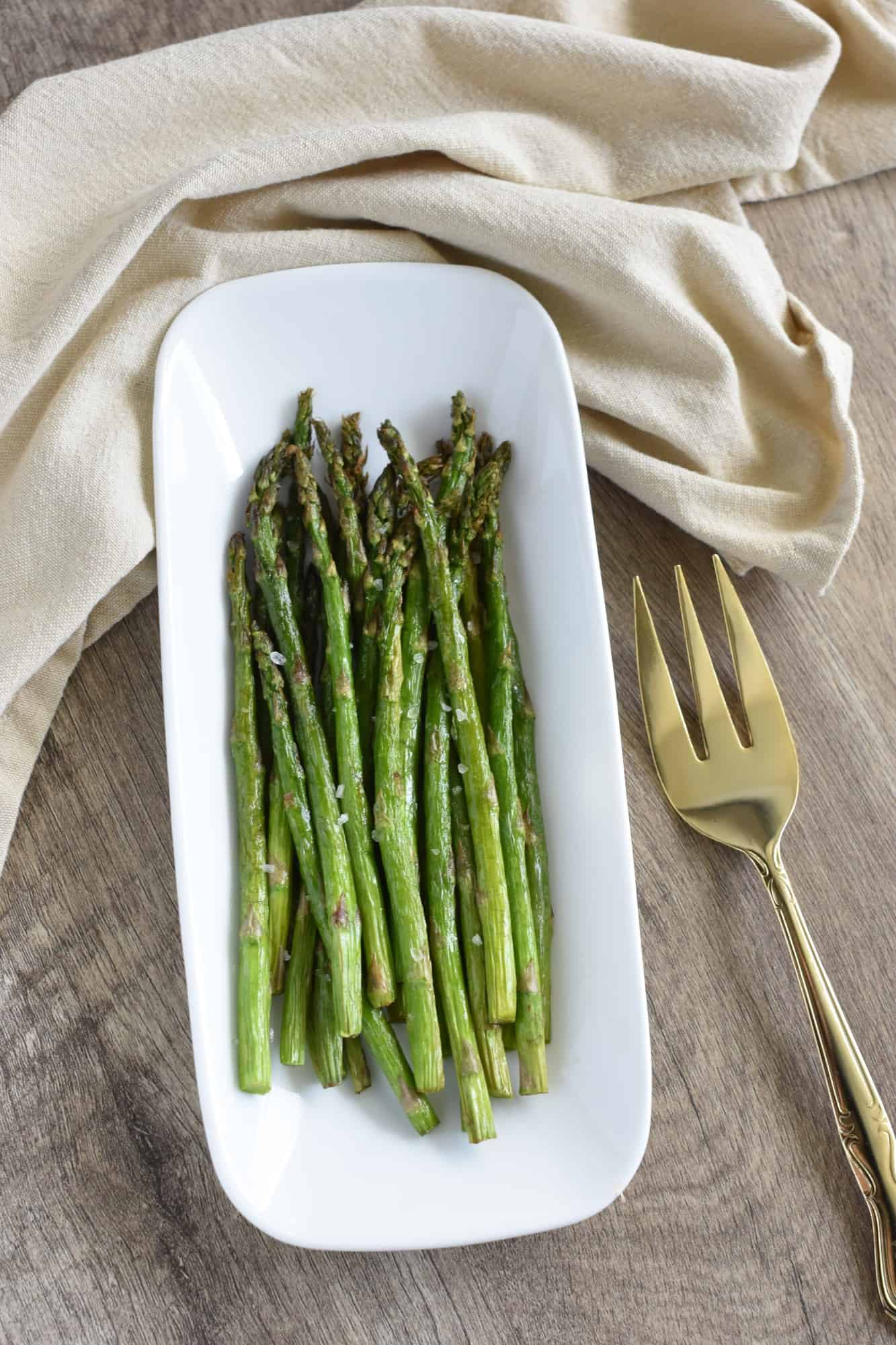 air fryer asparagus on white serving dish with fork next to it