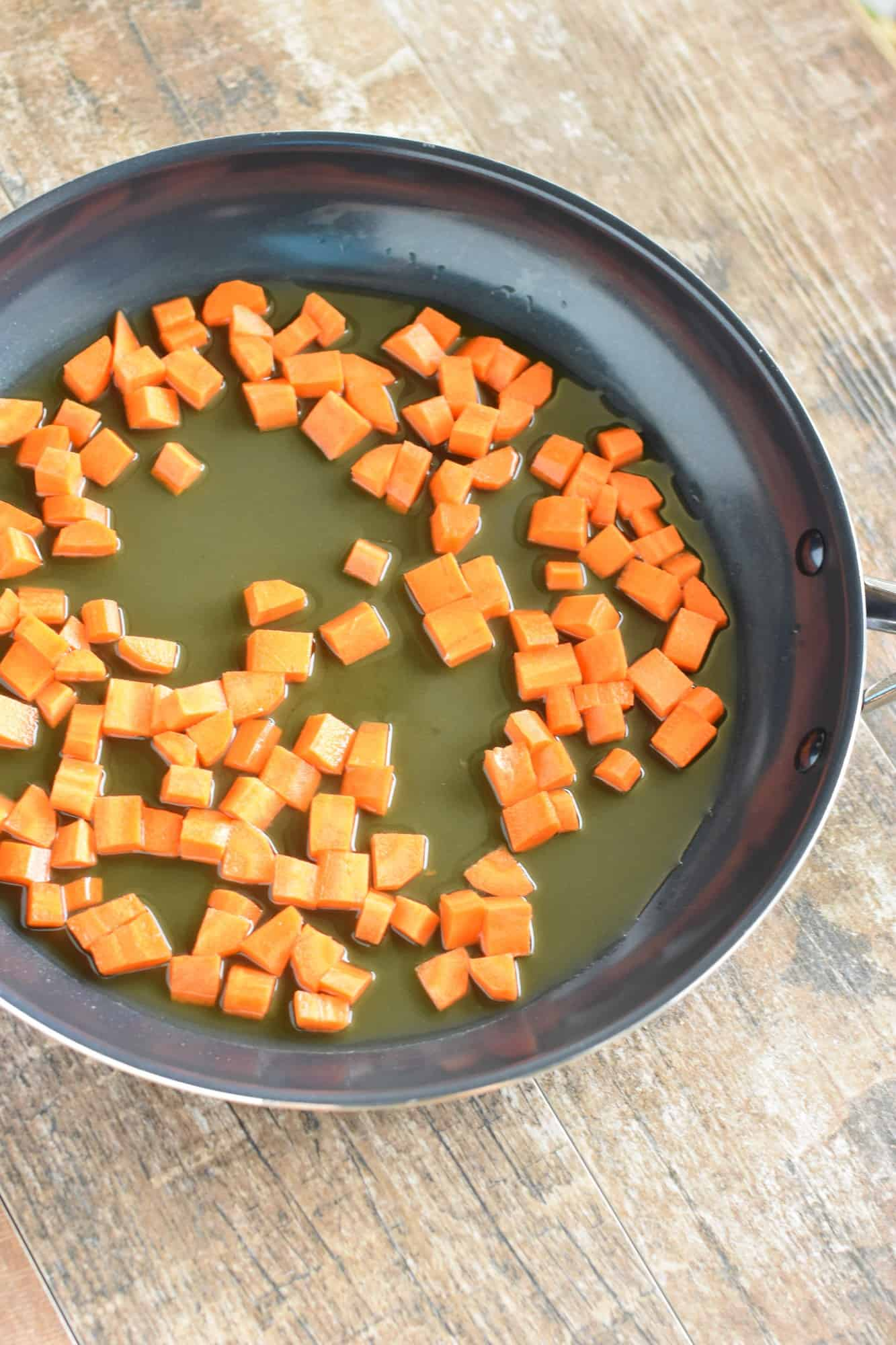 carrots cooking in vegetable broth in non-stick skillet
