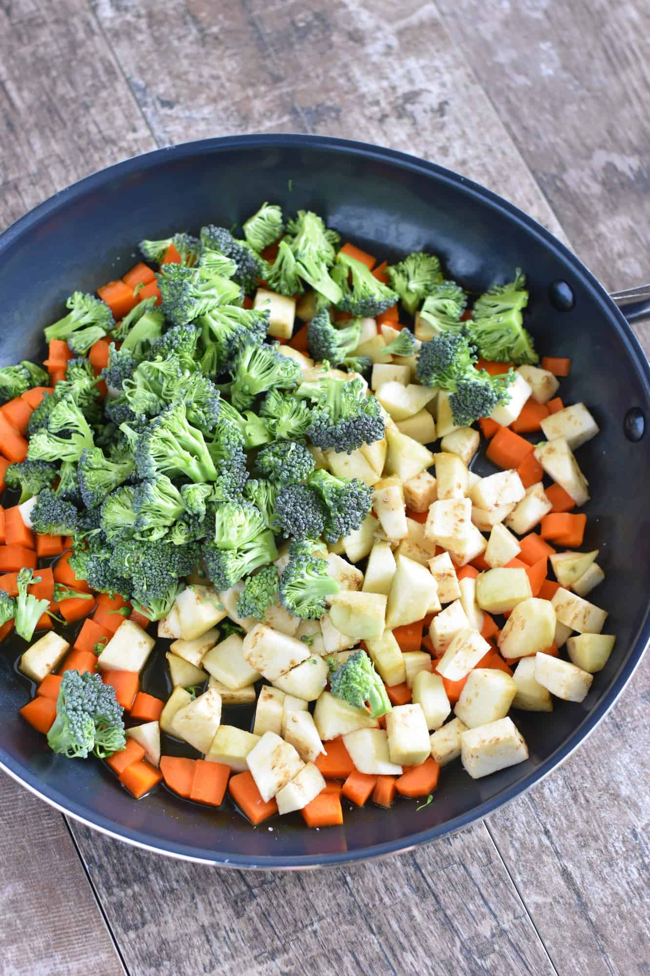broccoli and eggplant added to the carrots in the skillet