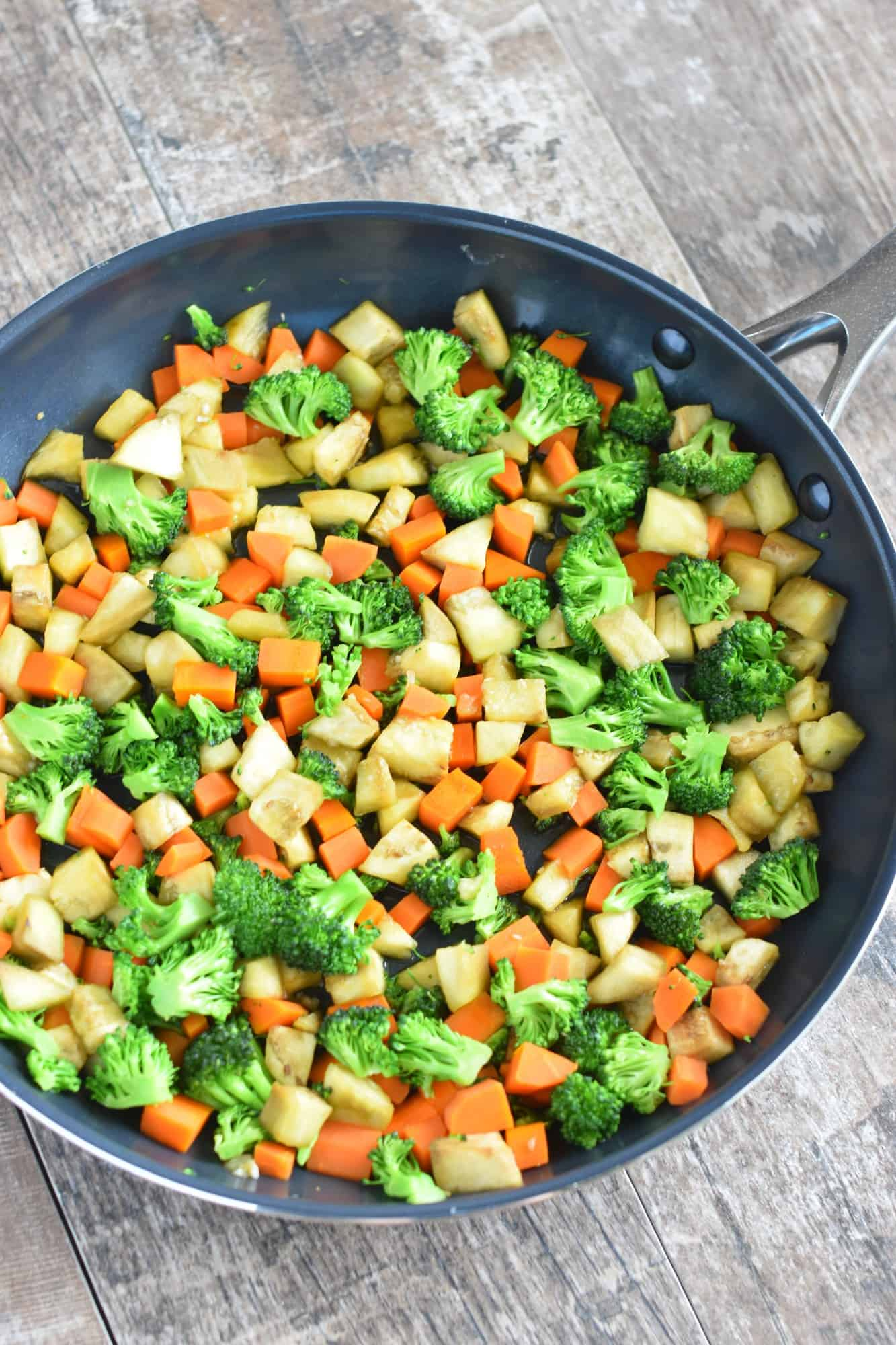 sauteed broccoli, eggplant and carrots in the skillet