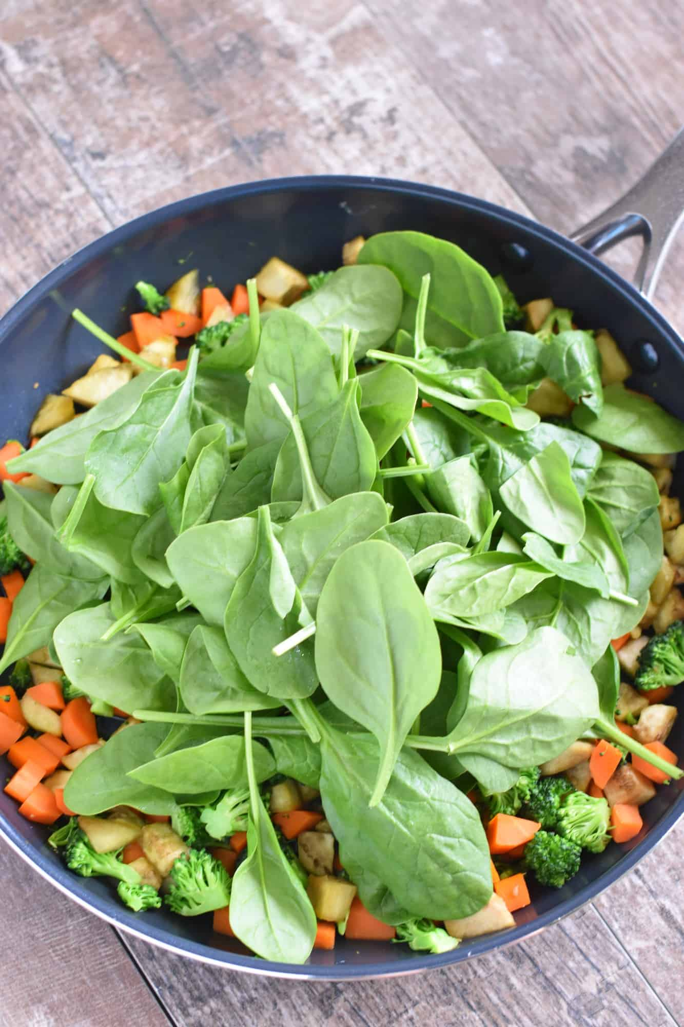 spinach added to the veggie mixture in the skillet