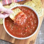 overhead shot of hand holding a chip with some of the salsa on it