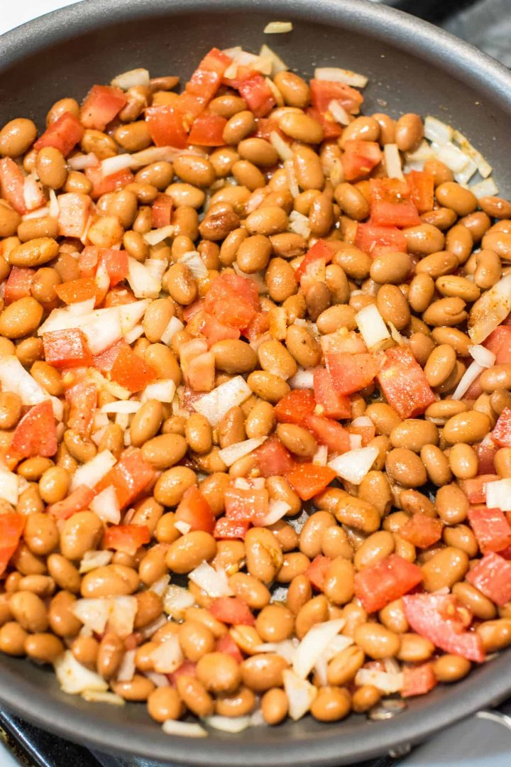 Beans, onions and tomatoes cooking in pan